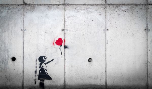image on concrete wall of small girl with arm outstretched, reaching toward a red heart-shaped ballon that has slipped from her grasp
